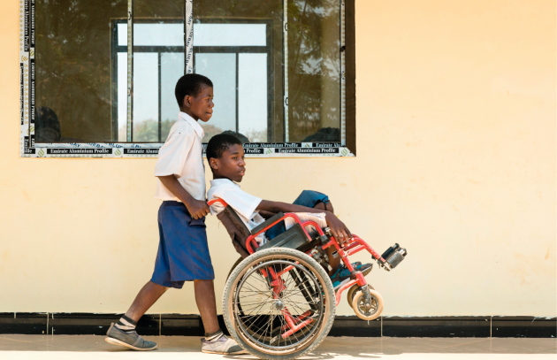 A boy pushing another boy in a wheelchair at a school in Tanzania.